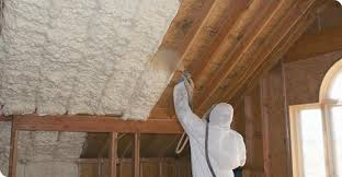 white spray foam being applied inside the roofing rafter