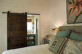 bedrooms bedroom idea with dark barn sliding door to bathroom and white cozy bed plus