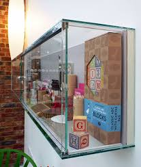 wide rectangular wall fixed glass display cabinet in mirror polished stainless steel and 6mm toughened glass with two lockable sliding doors and includes a