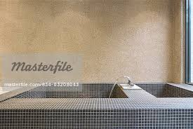 large mosaic tile bathtub with running water stock photo