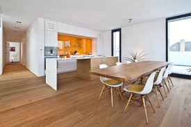dining room long rectangle brown wooden table with white plastic chairs with brown wooden legs