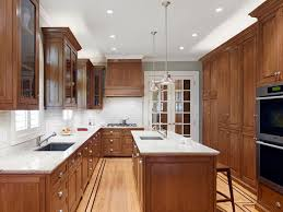 a kitchen with stained oak cabinets and white countertops