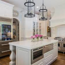 gray kitchen island with carved legs and stainless steel warming drawer