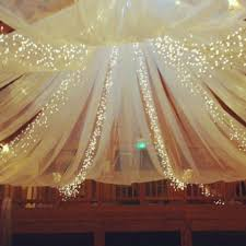 tulle and string lights in the barn barn wedding lighting
