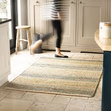 a natural fiber rug placed in a kitchen with a lady walking over it be