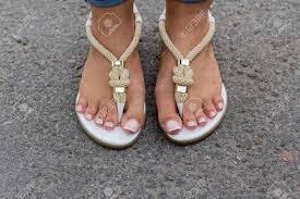 道路に美しいペディキュアのおしゃれなサンダルで足の女の子 の写真