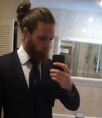 a photograph of a young businessman with a big manbun and a hipster beard style