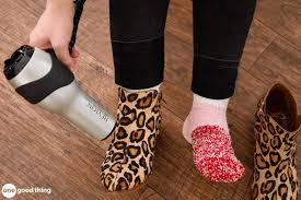 a pair of feet one wearing a cheetah print boot and the other wearing