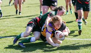 riley halvorson of the kamloops raiders drags brit lions tacklers with her as she scores a try in b c rugby union play at exhibition park on saay