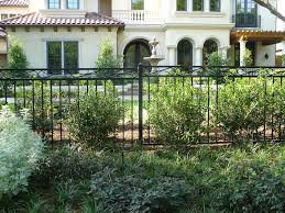 a diy wrought iron fence in front of a mediterranean home