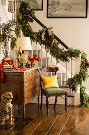 Fresh greenery entwined with pheasant feathers, pine cones and green ribbon  adorn the banister of this stairway. You can find the festive red with  accents ...