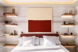 In this modern bedroom, four floating wood shelves with hidden lighting  have been installed,