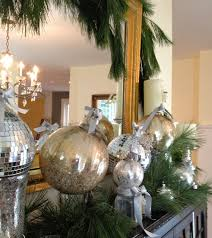decorating a mantel with evergreen garland and mercury glass tree decorations