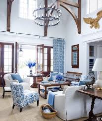 and doors open onto a loggia a lee jofa fl was used for the curtains and pair of victoria hagan slipper chairs the chandelier is by paul ferrante