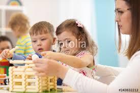 Nursery Teacher Children And Nursery Teacher Building Toy House In A Kindergarten