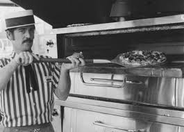 old tyme cook taking a pizza out of the oven