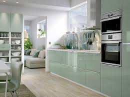 A medium size kitchen with light green high-gloss doors and drawers  combined with stainless