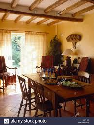 country dining room set. Old Wooden Chairs At Pine Table Set For Lunch In Beamed Country Dining Room With White Drapes On French Windows