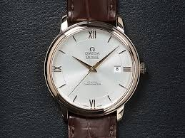 watch face of the gold de ville prestige watch with a white dial and brown leather