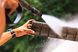 ac coil cleaner. a person holding an ac coil and spraying it clean with pressure washer cleaner