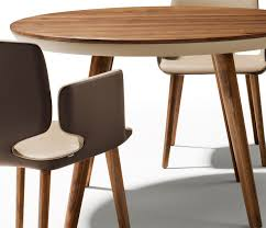 small high end luxury dining table showing the superb leather upholstered underbelly and walnut legs