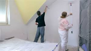 Couple painting new room. Man and woman working together painting room with  fresh white color