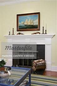 family room fireplace detail white painted mantel pale yellow walls nautical oil painting