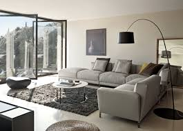 modern minimalist living room design with grey l shaped couch with recliner and round marble table with stainless steel legs plus dark gray fur rug and