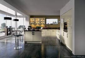 a modern kitchen with cream cabinets gray tile floors and a wide view of