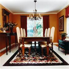 breathtaking glass living chandelier over luxurious dining set on colorful rugs white tiles flooring and small dresser with double red curatins windowed for