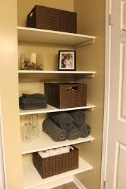 bathroom closet shelving. cant wait to update my closets with real shelves! km decor: diy: organizing open shelving in a bathroom boxes- same type, arranged facing different closet n