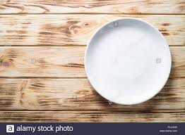 White Plate On Wooden Kitchen Table Top View Copy Space Stock Photo