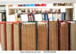 old books stand in a row on a shelf in the library 1059049898