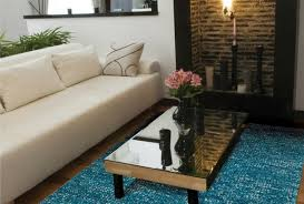 small space room with fireplace and blue rug and one long sofa with plant behind it