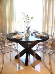 This elegant dining room features a large round wood dining table with  clear plastic Louis XVI