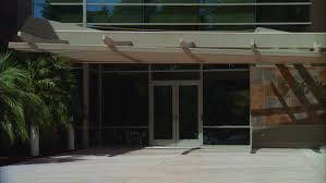 day tight glass doors entrance small long 2 story modern tan brown office building slate tile accents industrial commercial corporate park type large
