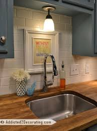 a white subway tile backsplash is a nice contrast to the gray cabinets butchers block