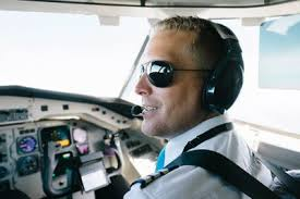 confident smiling pilot wearing ear sitting in pit