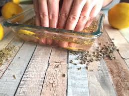 hands in herbal diy nail soak with lemons around