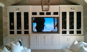 large white wooden cabinet having white wooden and black glass door plus  silver wall lamp and rectangle flat screen tv on white wooden wall.