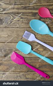 colorful kitchen utensils. Colorful Kitchen Utensils Arranged On A Wooden Table Top Background Forming Page Border