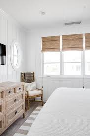 white cottage bedroom with shiplap walls featuring tan accents including a light brown dresser oil rubbed bronze cup pulls and a white and tan striped rug