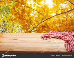 empty wooden deck table with tablecloth over bokeh autumn leaves background kitchen background