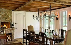 beautiful dining room with rustic wood beam ceiling accented with art deco chandeliers over farmhouse dining table lined with mismatched chairs as well as