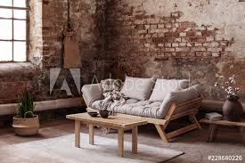 wooden table on rug in front of beige couch in apartment interior in wabi sabi style with red brick wall real photo