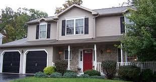tan house black shutters red door