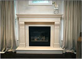 fireplace mantel kits under glass arch between double windows with tan solid curtains