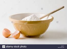 mixing bowl with flour and wooden spoon and broken egg