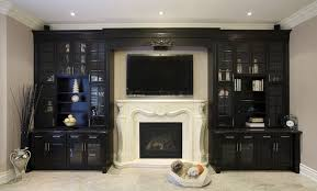 an entertainment center surrounds the plaster fireplace and the television that is mounted above it