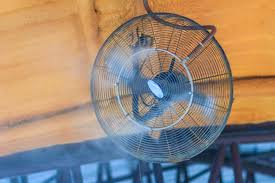 a wall mounted outdoor misting fan blowing a fine mist of cooling air
